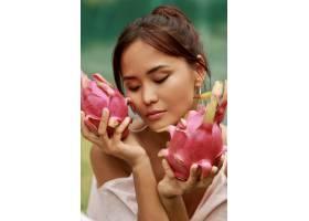 脸旁贴着火龙果的亚洲美女美人写真_9275572