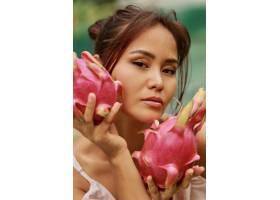 脸旁贴着火龙果的亚洲美女美人写真特写_9275574