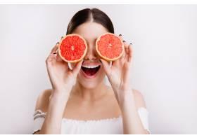 表情积极的快乐女孩用橙子遮住眼睛摆姿势_12607365