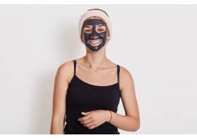 美丽的微笑着的女人脸上戴着黑色的粘土面_9416217