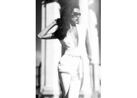 穿着白色西装戴着墨镜的时尚女商人在街上_6801983