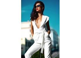 穿着白色西装戴着墨镜的时尚女模在街上_7249266
