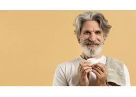 笑容可掬的留着胡须的年长男子拿着润肤霜_9411415