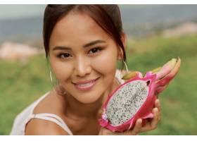 美丽的亚洲年轻女子手持火龙果的美人肖像_9275583