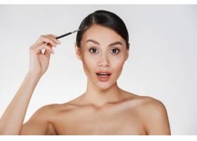 美丽的女人梳着发髻看着相机拿着画笔_6514595