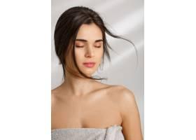 美丽的女人裹着柔软的毛巾闭着眼睛站着_8357971