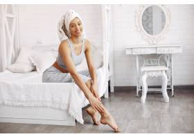 美丽的女孩坐在床上拿着美容产品_7169022
