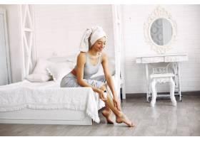 美丽的女孩坐在床上拿着美容产品_7169023