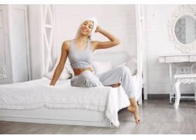 美丽的女孩坐在床上拿着美容产品_7169024