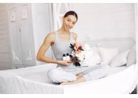 美丽的女孩坐在床上拿着美容产品_7169047