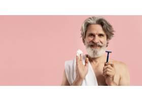 留着剃须刀和复印空间的资深胡须男子的前视_9411532