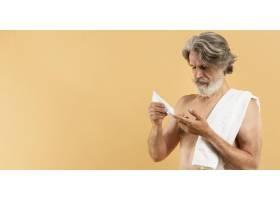 留着胡子的年长男子使用带有复印空间的奶油_9411481