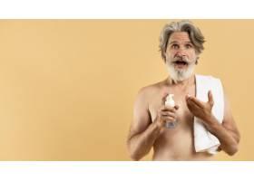 留着胡须的年长男子手持清洁剂的正视图_9411467