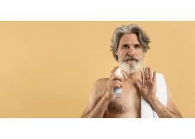 留着胡须的年长男子手持清洁剂的正视图带_9411474