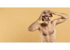 留着胡须的年长男子用复印空间指出皱纹_9411441