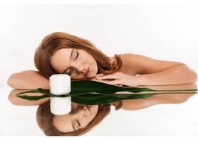 留着长发涂着润肤露和绿叶躺在镜台上的姜_6515111