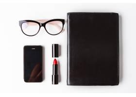 白色背景上有红色口红眼镜手机和笔记本_8757114
