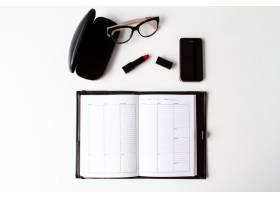 白色背景上的红色口红手机眼镜和笔记本_8757135