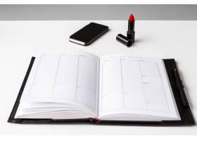 白色表面涂有红色口红的手机和笔记本_8757118