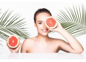 皮肤完美的年轻女子手持柑橘类水果周围环_8990774