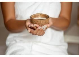 温泉沙龙里拿着椰子的女人的特写_8224513