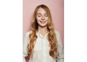 漂亮的年轻女子在粉色背景上摆姿势_6435509