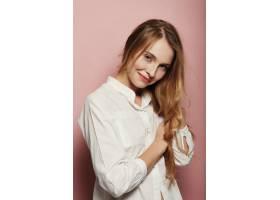 漂亮的年轻女子在粉色背景上摆姿势_6435531