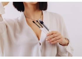 漂亮的年轻女生意人拿着化妆刷在朴素的墙上_8264108