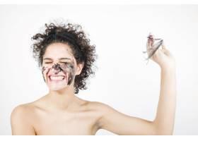 微笑快乐的年轻女子在白色背景下摘下面膜_3196206