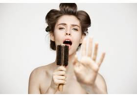 戴着卷发夹和毛巾的滑稽年轻女子在梳子里欢_9028379