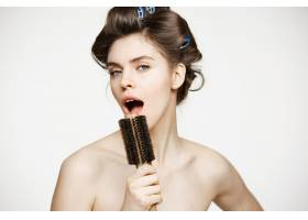 戴着卷发夹和毛巾的滑稽年轻女子在梳子里欢_9028381