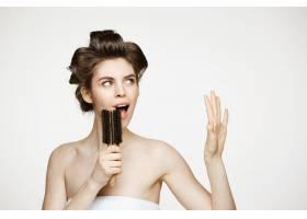 戴着卷发夹和毛巾的滑稽年轻女子在梳子里欢_9028384