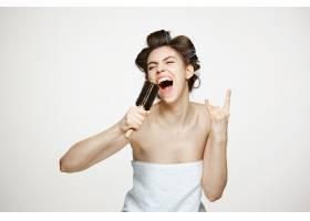 戴着卷发夹和毛巾的滑稽年轻女子在梳子里欢_9028387