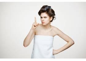 戴着卷发的年轻不悦女子的肖像美容美容和_9028352