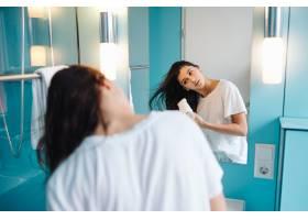 年轻女子在浴室里使用吹风机的肖像_8390138