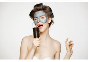 年轻滑稽女子的肖像戴着卷发和面膜在梳_9028467