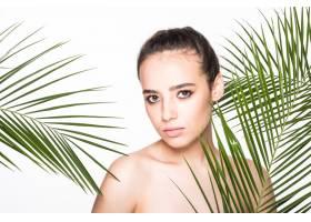 年轻的美女拿着绿色的棕榈叶摆姿势_8990716