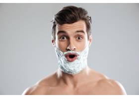 年轻的震惊男子脸上涂着剃须泡沫_8077993