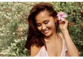 可爱的亚洲女人的夏日肖像头发上插着花_9275540