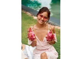 可爱的亚洲女子手里拿着粉红色的火龙果_9275569