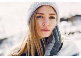 在白雪覆盖的田野上穿着毯子的年轻女孩_9331185