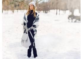 在白雪覆盖的田野上穿着毯子的年轻女孩_9331204