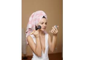 头上裹着毛巾的年轻美女在镜子里化妆_7252245