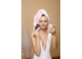 头上裹着毛巾的年轻美女在镜子里化妆_7252247