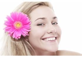 头发上戴着粉红色花朵的女人_7629996