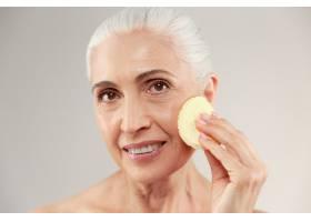 一位面带微笑的半裸老妇人的美丽肖像她用_7339972