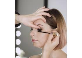一名女子在美丽的模特身上涂睫毛膏_6412677