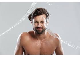 一名年轻男子孤零零地站在灰墙上洗脸_8078068