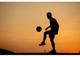 黄金时间日落时分一个男人踢足球的剪影_521228701