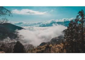 蓝天下云层之上的一座森林山的美丽镜头_997052601